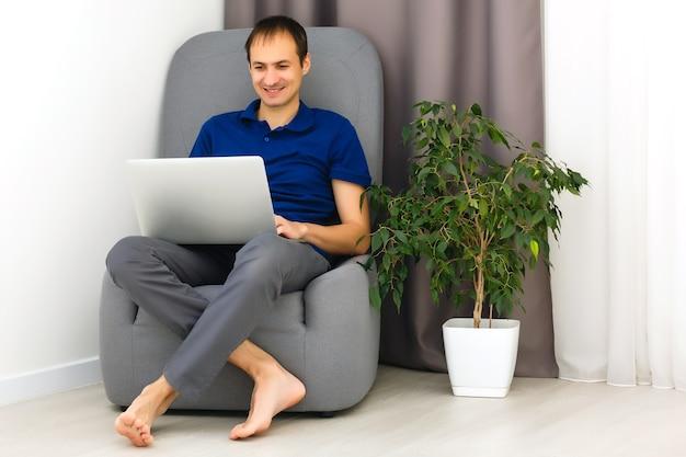 Glücklicher junger mann im t-shirt, der zu hause auf dem sofa sitzt und an laptop-computer arbeitet, lächelnd.