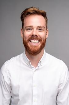 Glücklicher junger mann im weißen hemd mit den roten haaren und dem bart, die hell an der kamera auf grauem hintergrund lächeln