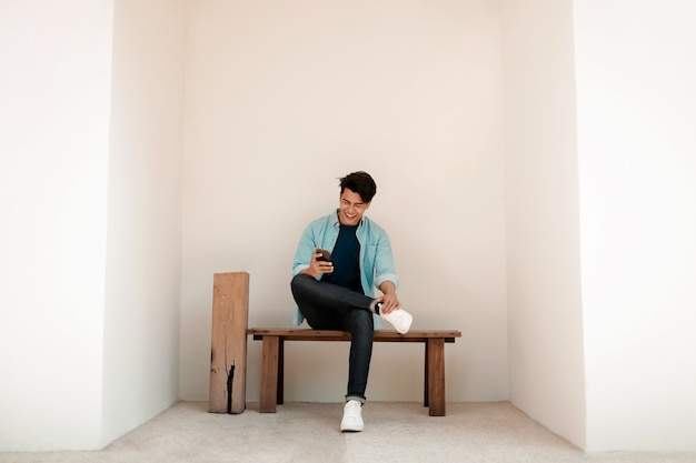 Glücklicher junger mann in der freizeitkleidung, die das handy beim sitzen auf der bank an der wand verwendet. lebensstil der modernen menschen.