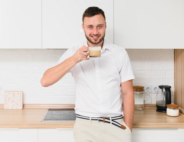 Glücklicher junger mann in der küche mit einem cappuccino