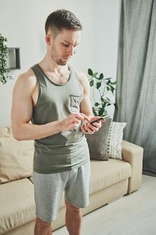Glücklicher junger mann in der sportbekleidung, die im smartphone während der suche nach online-videokurs der heimfitness beim stehen im wohnzimmer rollt