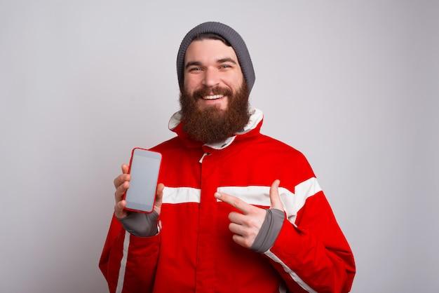 Glücklicher junger mann in der winterkleidung, die auf smartphone zeigt