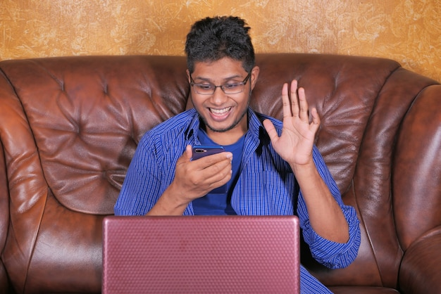Glücklicher junger mann in einer videokonferenz, die auf smartphone diskutiert.
