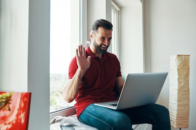 Glücklicher junger mann in freizeitkleidung mit laptop und winken beim sitzen auf der fensterbank