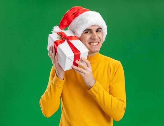 Glücklicher junger mann in gelbem rollkragenpullover und weihnachtsmütze mit lustiger krawatte, die ein geschenk hält, das kamera betrachtet, die fröhlich über grünem hintergrund steht