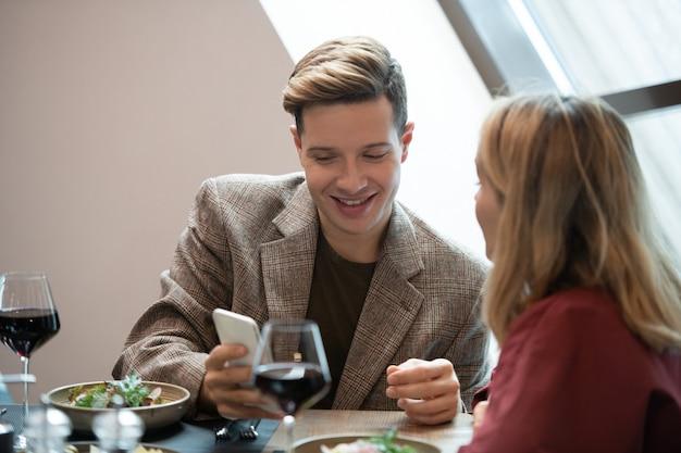 Glücklicher junger mann in intelligenter freizeitkleidung, der auf den bildschirm des smartphones schaut, während er ein neugieriges video sieht und es seiner freundin zeigt