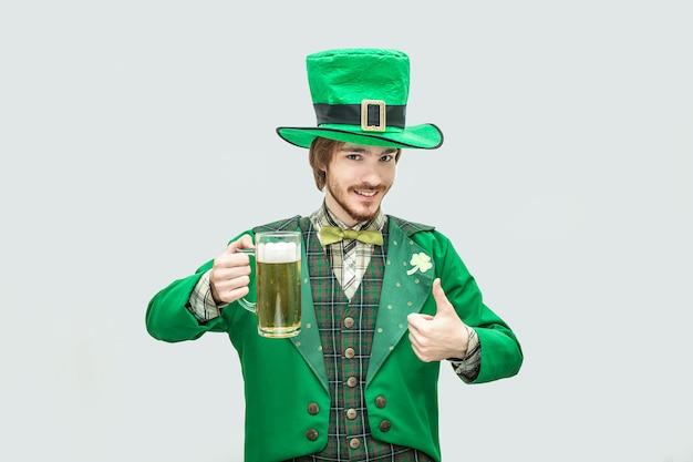 Glücklicher junger mann in st. patrick anzug halten krug bier und schauen. er hält einen großen daumen hoch. isoliert auf grau.