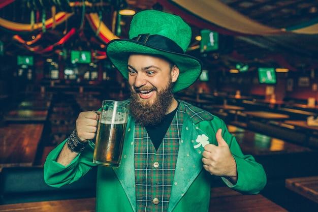 Glücklicher junger mann in st patrick anzug stehen in der kneipe und betrachten krug bier. er hält einen großen daumen hoch. junger mann sieht glücklich aus und lächelt.