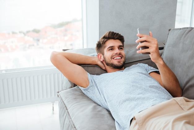 Glücklicher junger mann liegt auf bett und schaut am telefon.