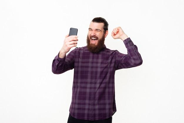 Glücklicher junger mann mit bart, der auf smartphone überrascht schaut und sieg feiert