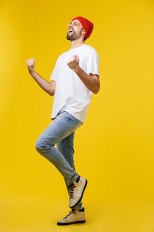 Glücklicher junger mann mit den armen oben lokalisiert auf einem gelb.