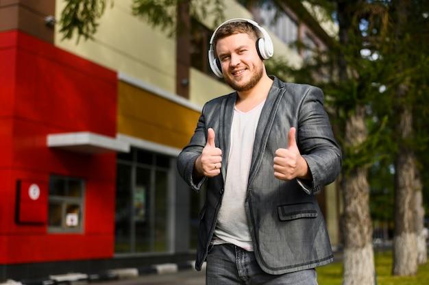 Glücklicher junger mann mit den kopfhörern, die kamera betrachten
