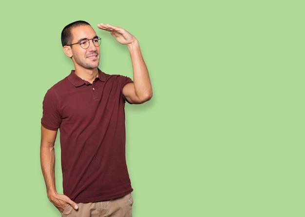 Glücklicher junger mann mit einer geste des wegschauens