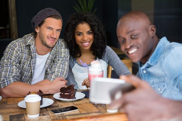 Glücklicher junger mann mit freunden, die selfie am hölzernen tisch im kaffeehaus nehmen