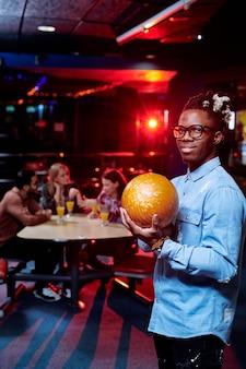 Glücklicher junger mann mit gelbem ball, der sie betrachtet, während sie ihn auf bowlingbahn während des spiels im freizeitzentrum werfen
