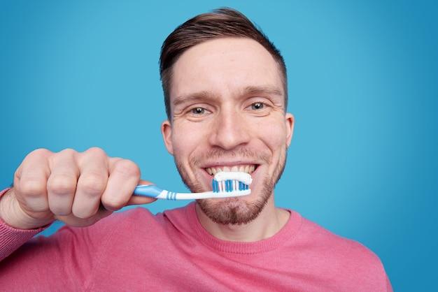 Glücklicher junger mann mit gesundem lächeln, das seine zähne putzt, während zahnbürste durch mund isoliert gehalten wird