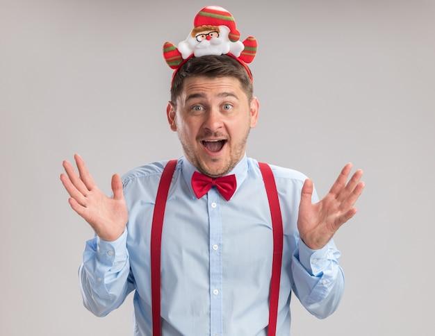 Glücklicher junger mann mit hosenträgerfliege in felge mit weihnachtsmann, der erstaunt und überrascht in die kamera schaut, die über weißem hintergrund steht