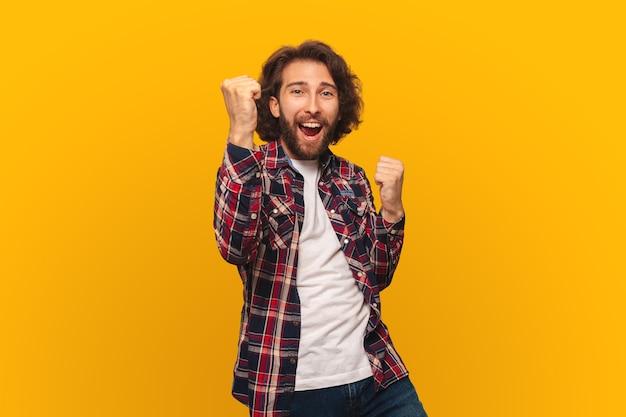 Glücklicher junger mann mit langen haaren in einem hemd feiert den sieg mit erhobenen armen auf einem leuchtend gelben hintergrund