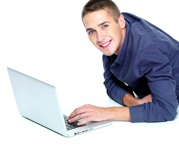 Glücklicher junger mann mit laptop lokalisiert auf weiß
