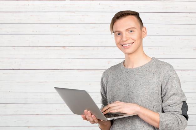 Glücklicher junger mann mit laptop