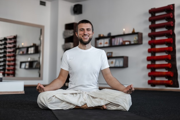 Glücklicher junger mann mit positivem lächeln mit bart, der yoga im fitness-studio praktiziert. gesunder lebensstil.