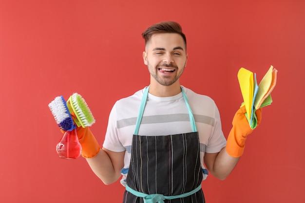 Glücklicher junger mann mit reinigungsmitteln auf farbe