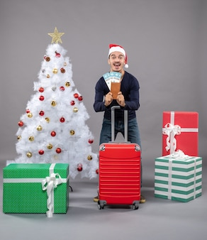 Glücklicher junger mann mit rotem koffer, der seine reisetickets auf grau zeigt