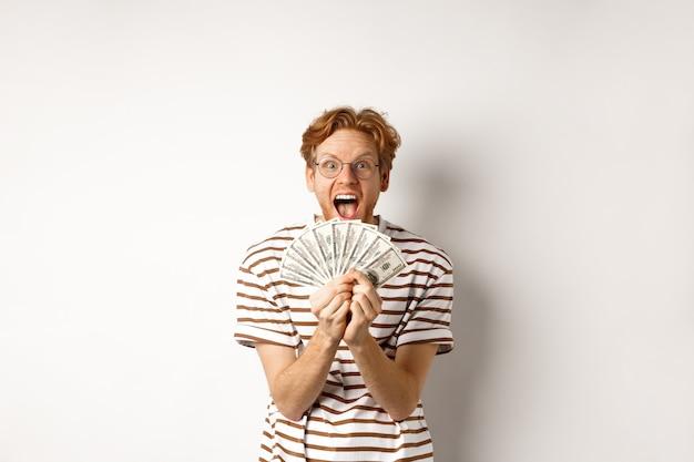 Glücklicher junger mann mit roten haaren, der dollar zeigt, geld gewinnt und vor glück schreit, preisgeld hält und auf weißem hintergrund steht