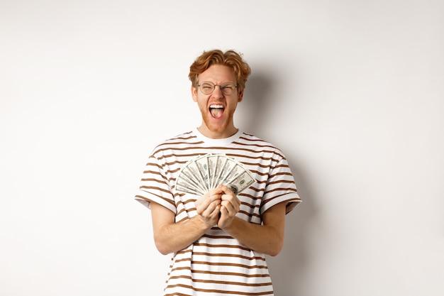 Glücklicher junger mann mit roten haaren, der dollar zeigt, geld gewinnt und vor glück schreit, preisgeld hält und auf weißem hintergrund steht.