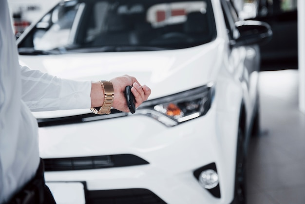 Glücklicher junger mann mit schlüsseln in seinen händen, glück, ein auto zu kaufen.