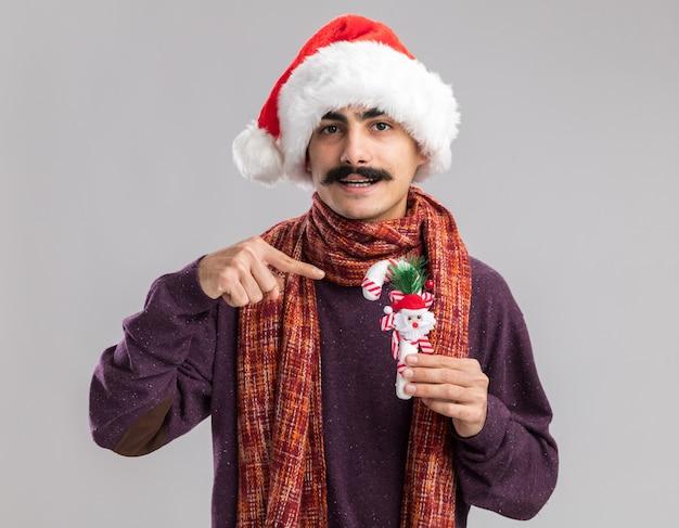 Glücklicher junger mann mit schnurrbart, der weihnachtsmann-weihnachtsmütze mit warmem schal um seinen hals trägt, der weihnachts-zuckerstange hält, die mit zeigefinger lächelnd darauf zeigt
