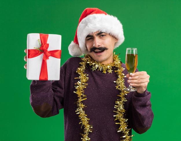Glücklicher junger mann mit schnurrbart, der weihnachtsweihnachtsmütze mit lametta um seinen hals trägt, der glas champagner und weihnachtsgeschenk hält und kamera betrachtet, die fröhlich über grünem hintergrund steht