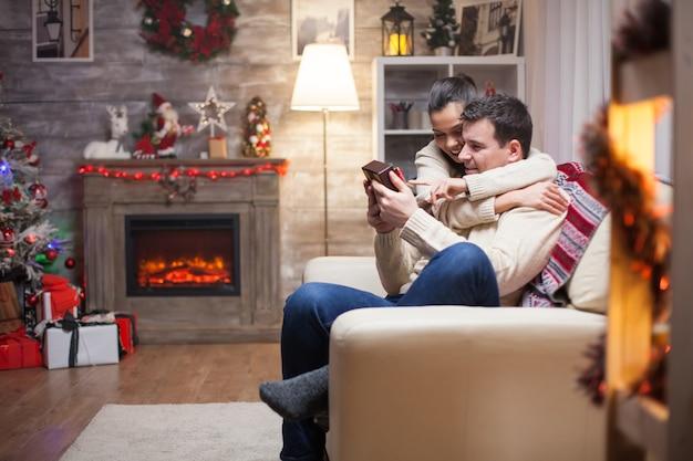 Glücklicher junger mann mit seinem geschenk von frau am weihnachtstag sitzt auf der couch mit kamin im wohnzimmer.