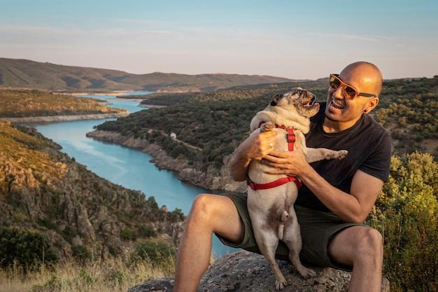 Glücklicher junger mann mit seinem hund im berg
