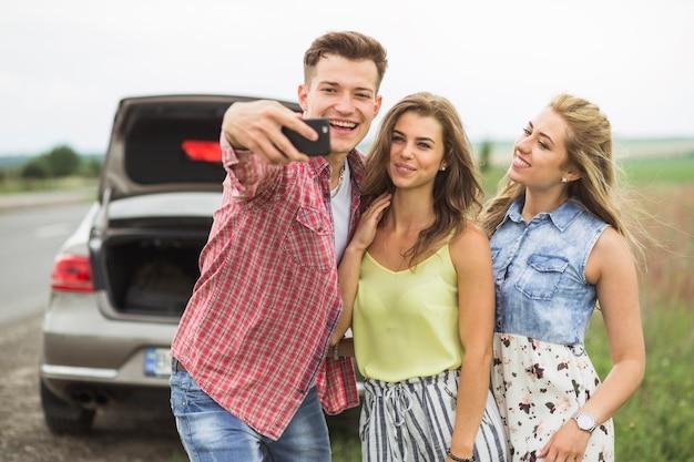 Glücklicher junger mann mit seinen freunden, die selbstporträt durch handy nehmen