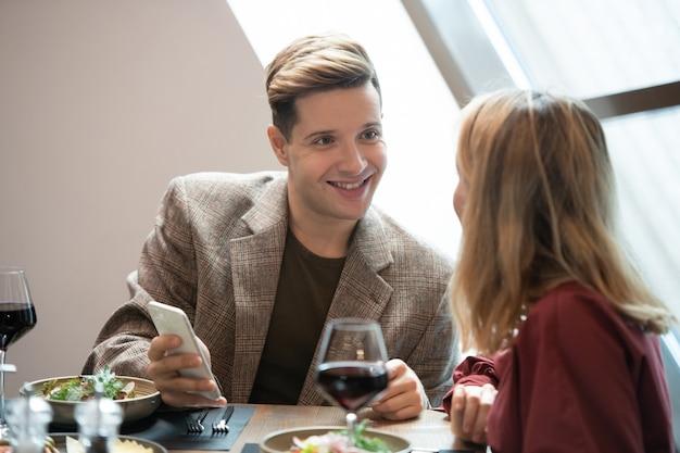 Glücklicher junger mann mit smartphone, der seine freundin mit einem lächeln ansieht, während er mit ihr am bedienten tisch im luxuriösen restaurant spricht?