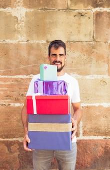 Glücklicher junger mann mit staplungsgeschenken gegen schmutzwand