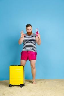 Glücklicher junger mann mit tasche, die für das reisen auf blauem raum vorbereitet wird