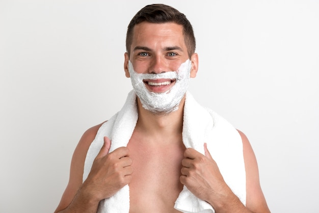 Glücklicher junger mann mit tuch traf das rasieren des schaums auf seinem gesicht zu, das gegen wand steht