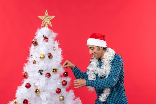 Glücklicher junger mann mit weihnachtsmannhut in einem blauen gestreiften hemd und, das seinen weihnachtsbaum auf rot verziert