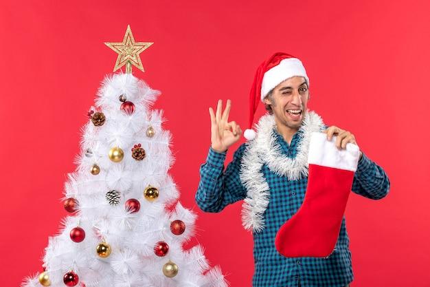 Glücklicher junger mann mit weihnachtsmannhut in einem blauen gestreiften hemd