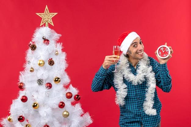 Glücklicher junger mann mit weihnachtsmannhut und hält ein glas wein und uhr nahe weihnachtsbaum auf rot