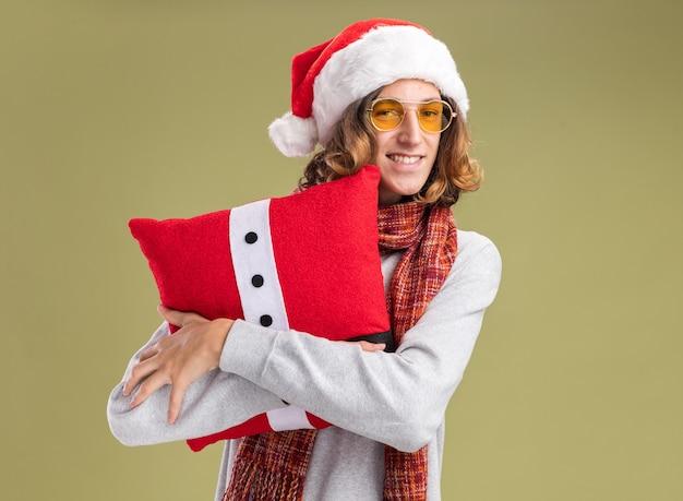 Glücklicher junger mann mit weihnachtsmütze und gelber brille mit warmem schal um den hals, der ein weihnachtskissen mit einem lächeln auf dem gesicht über der grünen wand hält