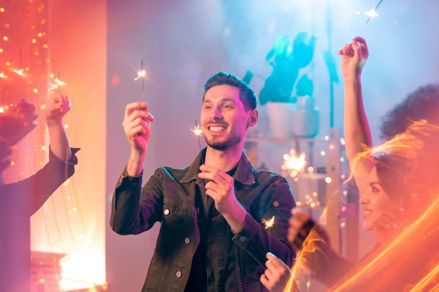 Glücklicher junger mann mit zahnigem lächeln, das funkelnde bengalische lichter in seinen händen betrachtet, während spaß mit freunden an der neujahrs-hausparty hat