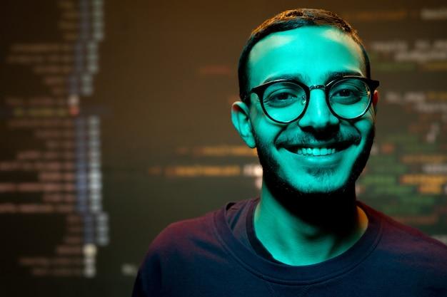 Glücklicher junger mann mit zahnigem lächeln, das gegen großen bildschirm mit entschlüsselten informationen steht