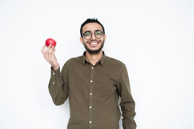 Glücklicher junger mann mit zahnigem lächeln, das reifen roten apfel in der rechten hand hält, während vor kamera steht