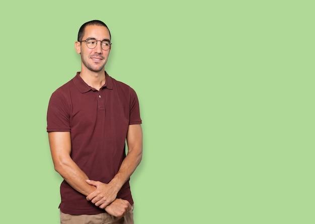 Glücklicher junger mann posiert vor hintergrund