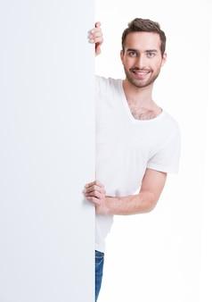 Glücklicher junger mann schauen aus leerem banner heraus - lokalisiert auf weiß