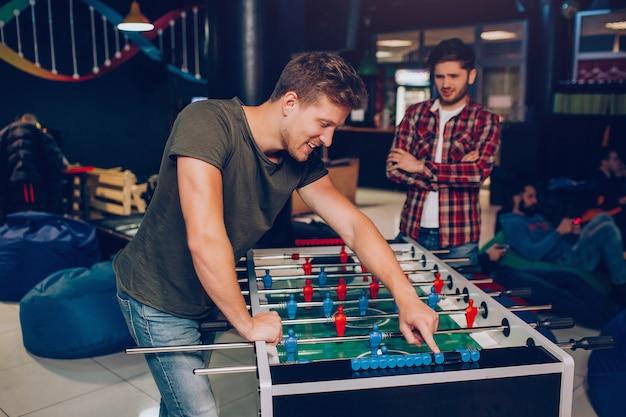 Glücklicher junger mann stehen und an tischfußball im spielzimmer lehnen. sein unglücklicher freund steht dahinter. er hält die hände gekreuzt.