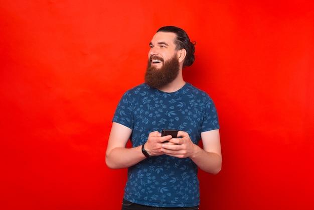 Glücklicher junger mann tippt auf seinem telefon über rotem hintergrund.
